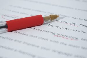 A red pen resting on a piece of paper with edits.
