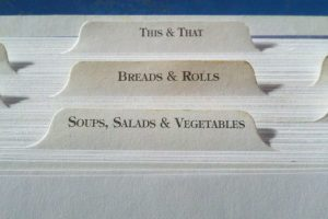 Three tabs in a recipe box, each representing a different recipe card. One is labelled soups, salads and vegetables; the second is labelled breads and rolls, and the third is labelled this and that.